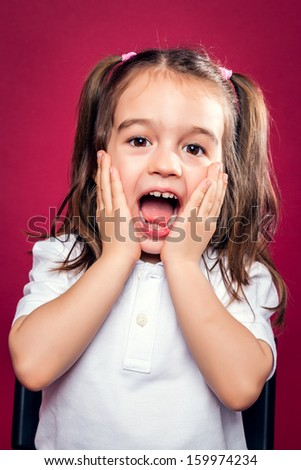 Funny Little Girl wit Surprise Expression Over Red Background