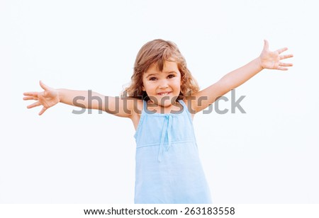 Funny little girl with arms outstretched - stock photo