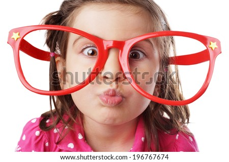 Funny little girl with big red glasses making face - stock photo