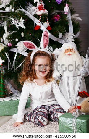 Funny little girl with bunny ears. Portrait of Beautiful little girl with long in headband bunny. Little Bunny. Portrait of a lovely little girl among Christmas decorations
