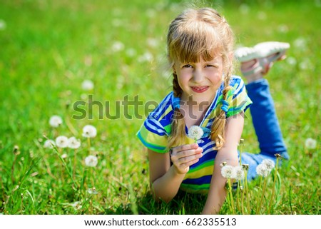 Funny little girl with dandelions in a summer park. Sunny day.