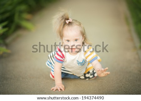 funny little girl with Down syndrome creeps along the path - stock photo