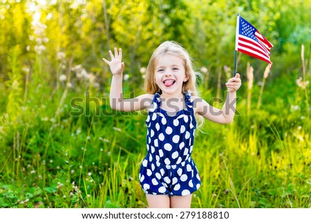 Funny little girl with long curly blond hair putting out her tongue and waving american flag, outdoor portrait on sunny day in summer park. Independence Day, Flag Day concept