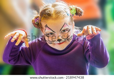 Funny little girl with painted face - stock photo