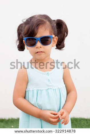Funny little girl with pigtails and blue dress outdoor - stock photo