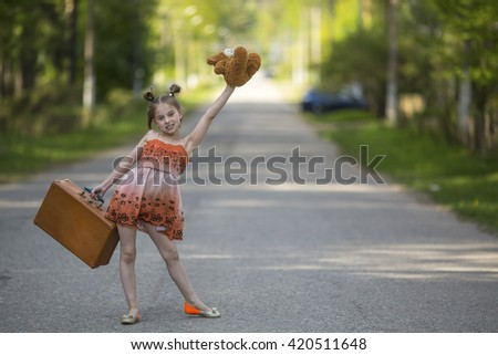 Funny little girl with suitcase and Teddy bear is on the road. - stock photo