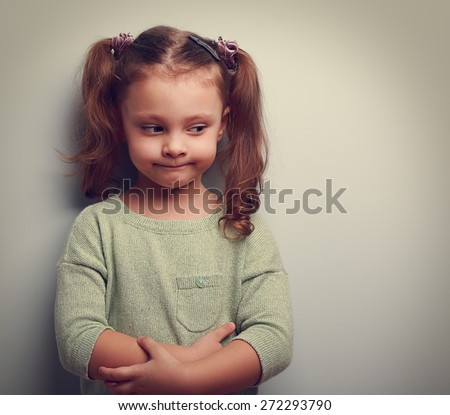 Funny little girl with thinking face looking with empty copy space. Vintage closeup portrait - stock photo