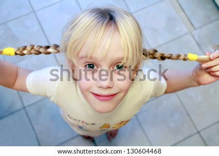 Funny little girl with two braids  Looking up