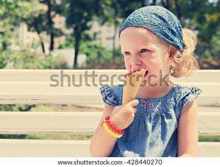 Funny little girl (3 years) eat ice cream. Selective focus. - stock photo