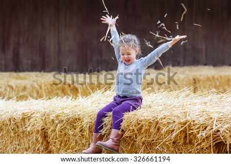 Funny little happy girl having fun with hay on a farm. Child enjoying autumn season and laughing. Happy childhood, lifestyle concept. - stock photo
