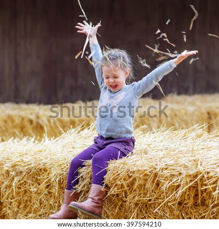 Funny little happy girl having fun with hay on a farm. Child enjoying autumn season and laughing. Happy childhood, lifestyle concept.