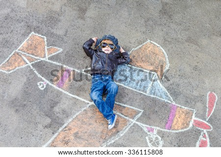Funny little kid boy flying by a plane picture painting with colorful chalk. Creative leisure for children outdoors in summer. - stock photo