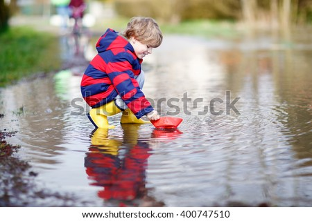 Funny little kid boy in rain boots playing with paper ship by a puddle on warm spring day. Active leisure for children. Child having fun outdoors. - stock photo
