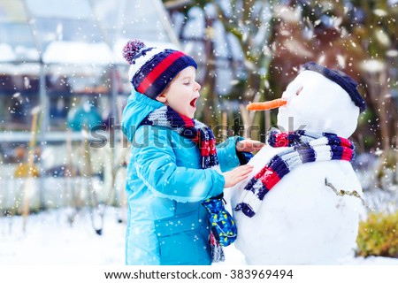 Funny little kid boy making a snowman and eating carrot. child playing and having fun with snow on cold day. Active outdoors leisure with kids in winter. - stock photo
