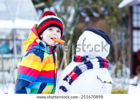Funny little kid boy making a snowman and eating carrot, playing and having fun with snow, outdoors  on cold day. Active outoors leisure with children in winter. - stock photo