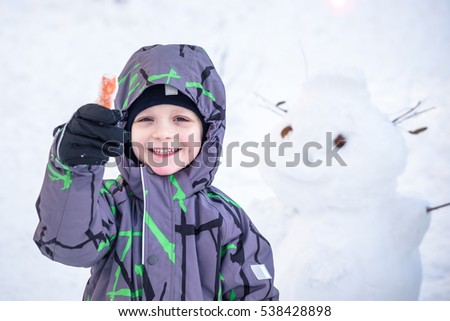 Funny little kid boy making a snowman and eating carrot, playing and having fun with snow, outdoors on cold day. Active leisure with children in winter. Happy smiling child boy kid