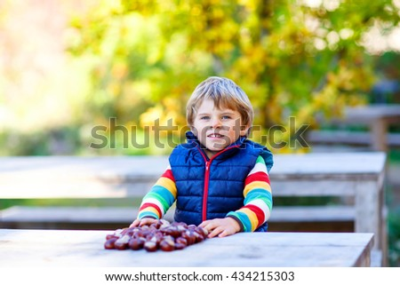 Funny little kid boy of 3 years playing with chestnuts in autumn park. Child having fun on cold fall sunny day. Happy childhood and outdoor leisure concept. With yellow foliage on background