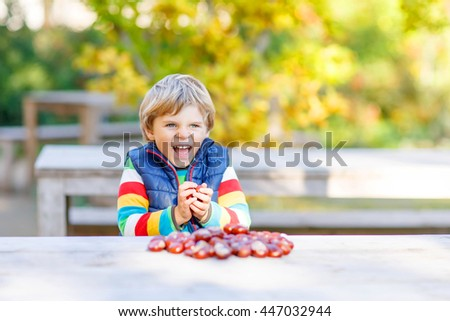 Funny little kid boy of 3 years playing with chestnuts in autumn park. Child having fun on cold fall sunny day. Happy childhood and outdoor leisure concept. With yellow foliage on background - stock photo