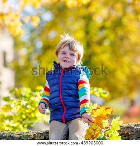 Funny little kid boy of 3 years playing with yellow maple leaves in autumn park. Child having fun on cold fall sunny day. Happy childhood and outdoor leisure concept. With golden foliage on background - stock photo
