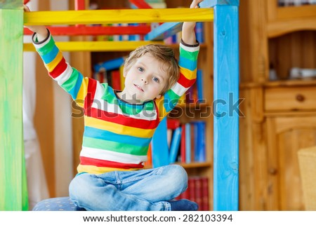 Funny little kid boy playing in selfmade wooden colorful house. child having fun indoors. Boy wearing colorful shirt with stripes. - stock photo