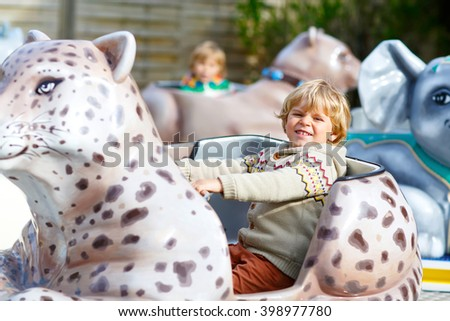 Funny little kid boy riding on animal on roundabout carousel in amusement park. Happy toddler having fun outdoors on sunny day. - stock photo