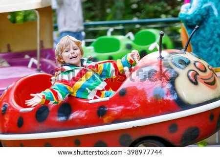 Funny little kid boy riding on ladybug animal on roundabout carousel in amusement park. Happy preschool child having fun outdoors on sunny day. - stock photo