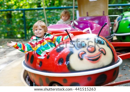 Funny little kid boy riding on ladybug animal on roundabout carousel in amusement park. Happy preschool child having fun outdoors on sunny day.