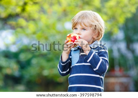 Funny little kid boy with apple on his first day to elementary school or nursery. Outdoors.  Back to school, kids, lifestyle concept. Child eating healthy food - stock photo