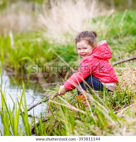 Funny little kid girl with dandelion flowers wreath playing in nature on spring day. Child having fun in forest, outdoors