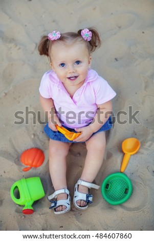 funny little kid playing in the sand. Top view. The concept of childhood and development.