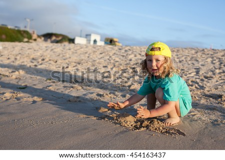 Funny little kid playing on sandy beach
