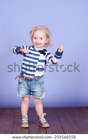 Funny little kids girl 2-3 year old dancing in room over purple. wearing stylish striped shirt and denim shorts. Childhood. - stock photo