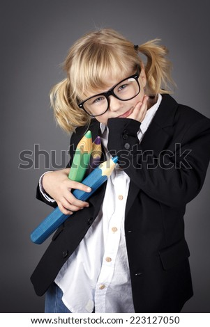 Funny little nerd holding big coloring pencils - stock photo
