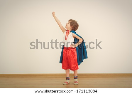 Funny little power super hero child (boy) in a blue raincoat.  Superhero concept - stock photo