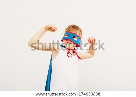 Funny little power super hero child (boy) in a blue raincoat.  Superhero concept - stock photo