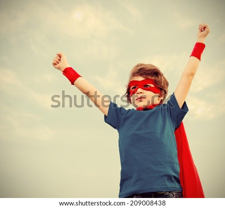 Funny little power super hero child (boy) in a red raincoat. Superhero concept - stock photo