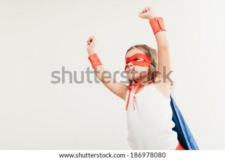 Funny little power super hero child (girl) in a blue cloak. Superhero concept. - stock photo