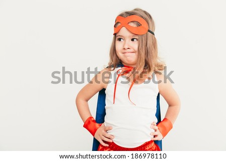 Funny little power super hero child (girl) in a blue cloak. Superhero concept. - stock photo