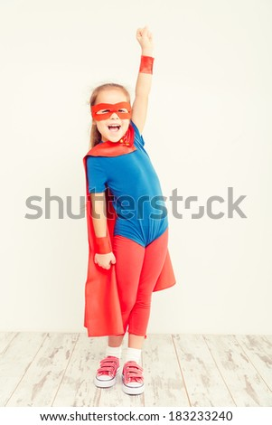 Funny little power super hero child (girl) in a blue raincoat. Superhero concept - stock photo