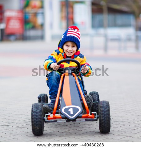 Funny little preschool kid boy having fun with toy race car, outdoors. Child driving car. Outdoor games for children concept. On spring or autumn day. - stock photo