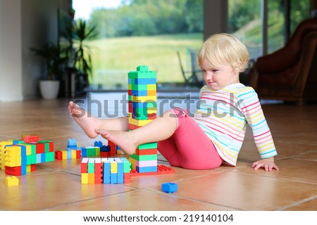 Funny little preschooler child, cute blonde toddler girl playing with plastic bricks sitting indoors on a tiles floor - stock photo