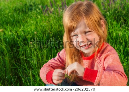 funny little red-haired girl sitting in the green grass - stock photo