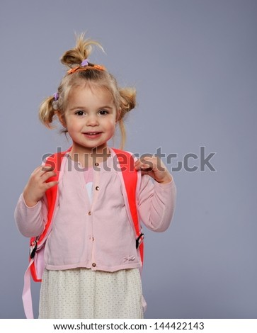 Funny little school girl with a backpack isolated on grey