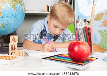Funny little schoolboy studying in classroom - stock photo