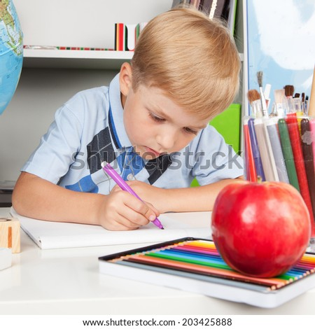 Funny little schoolboy studying in classroom