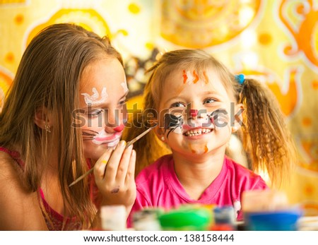 Funny little sisters playing with painting. - stock photo