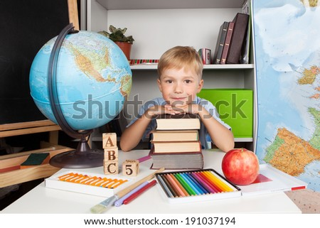 Funny little smiling schoolboy studying in classroom