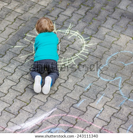 Funny little toddler boy painting sun with colorful chalks outdoors in summer. Kid having fun. Creative leisure with children outdoors. - stock photo