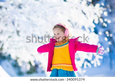 Funny little toddler girl in a colorful knitted hat and warm coat playing with snow. Kids play outdoors in winter. Children having fun at Christmas time. Child enjoying sunny day during Xmas vacation. - stock photo