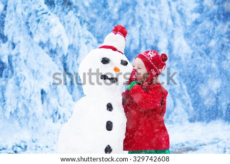 Funny little toddler girl in a red knitted Nordic hat and warm coat playing with a snow man. Kids play outdoors in winter. Children having fun at Christmas time. Child building snowman at Xmas. - stock photo